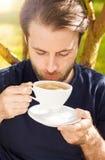 Café de consumición del hombre caucásico en el jardín Foto de archivo