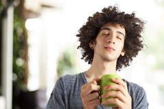 Café de consumición del hombre joven al aire libre Foto de archivo