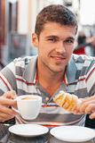 Café de consumición del hombre joven con el cruasán Fotos de archivo libres de regalías
