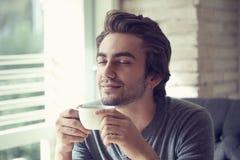 Café de consumición del hombre joven en café Fotografía de archivo libre de regalías