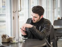 Café de consumición del hombre joven mientras que mira el teléfono imagenes de archivo