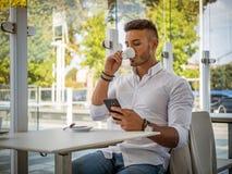 Café de consumición del hombre joven mientras que mira el teléfono móvil imagen de archivo