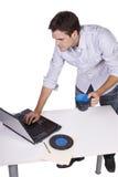 Café de consumición del hombre joven y trabajo en la computadora portátil Imagen de archivo