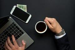 Café de consumición del hombre mientras que trabaja Imagen de archivo libre de regalías