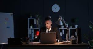 Café de consumición del hombre de negocios cansado y trabajo en el ordenador portátil en la noche metrajes