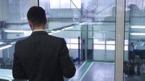 Café de consumición del hombre de negocios joven y mirada fuera de ventana almacen de video