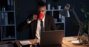 Café de consumición del hombre de negocios y trabajo en el ordenador portátil en la noche almacen de metraje de vídeo