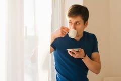 Café de consumición del hombre que mira hacia fuera la ventana Fotos de archivo