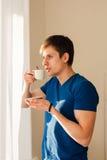 Café de consumición del hombre que mira hacia fuera la ventana Fotografía de archivo libre de regalías
