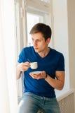 Café de consumición del hombre que mira hacia fuera la ventana Imagen de archivo libre de regalías