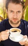 Café de consumición del hombre serio en el jardín Foto de archivo