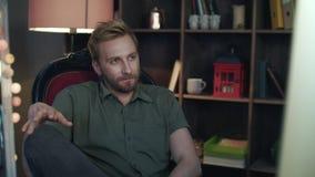 Café de consumición del hombre y disfrutar del trabajo Hombre que mira el monitor en estudio acogedor metrajes