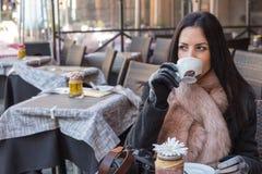 Café de consumición del pensamiento y de la mujer positiva por la mañana y el s Fotografía de archivo