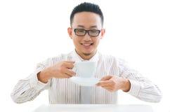 Café de consumición del varón asiático del negocio Imagen de archivo libre de regalías