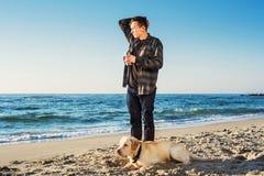 Café de consumición del varón caucásico joven mientras que camina con el perro imágenes de archivo libres de regalías