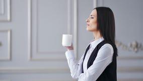 Café de consumición elegante acertado de la mujer de negocios de la vista lateral en el interior de lujo almacen de metraje de vídeo