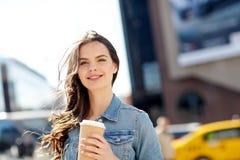 Café de consumición feliz de la mujer joven en la calle de la ciudad Fotos de archivo libres de regalías