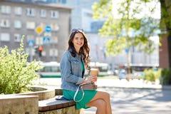 Café de consumición feliz de la mujer joven en la calle de la ciudad Imagen de archivo libre de regalías