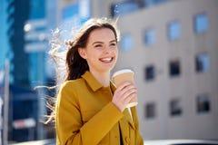 Café de consumición feliz de la mujer joven en la calle de la ciudad Imagenes de archivo