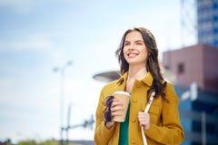 Café de consumición feliz de la mujer joven en la calle de la ciudad Foto de archivo