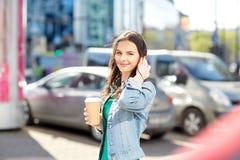 Café de consumición feliz de la mujer joven en la calle de la ciudad Fotografía de archivo
