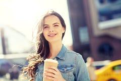 Café de consumición feliz de la mujer joven en la calle de la ciudad Imagen de archivo