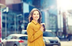 Café de consumición feliz de la mujer joven en la calle de la ciudad Foto de archivo libre de regalías