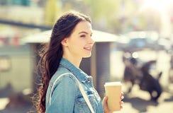 Café de consumición feliz de la mujer joven en la calle de la ciudad Imágenes de archivo libres de regalías