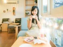 Café de consumición hermoso asiático de la mujer joven cerca de la ventana Fotos de archivo
