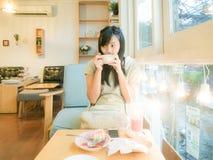 Café de consumición hermoso asiático de la mujer joven cerca de la ventana Imágenes de archivo libres de regalías