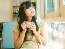 Café de consumición hermoso asiático de la mujer joven cerca de la ventana Fotografía de archivo
