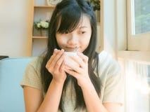 Café de consumición hermoso asiático de la mujer joven cerca de la ventana Imagen de archivo libre de regalías