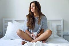 Café de consumición hermoso de la mujer joven en la cama foto de archivo