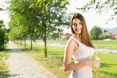Café de consumición hermoso de la mujer joven en parque Imagen de archivo libre de regalías