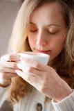 Café de consumición hermoso de la mujer joven. Taza de bebida caliente Fotos de archivo libres de regalías