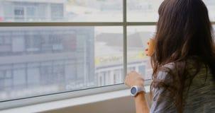 Café de consumición de la empresaria mientras que se sienta cerca de ventana en la oficina 4k metrajes