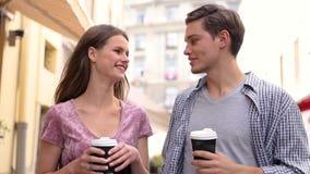 Café de consumición de la gente joven y el caminar en la calle de la ciudad metrajes