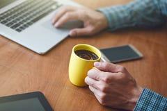Café de consumición de la mañana del hombre con el ordenador portátil Fotos de archivo