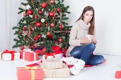 Café de consumición de la muchacha debajo del té del Año Nuevo del árbol de navidad Fotos de archivo
