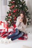 Café de consumición de la muchacha debajo del té del Año Nuevo del árbol de navidad Foto de archivo