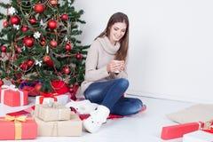 Café de consumición de la muchacha debajo del té del Año Nuevo del árbol de navidad Imagenes de archivo