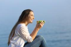 Café de consumición de la muchacha feliz que mira lejos en la playa Fotos de archivo