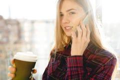 Café de consumición de la muchacha hermosa joven y el hablar en el teléfono, mujer en un edificio de oficinas imagen de archivo