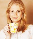 Café de consumición de la muchacha rubia linda joven cercano para arriba en el CCB caliente del marrón Fotos de archivo libres de regalías