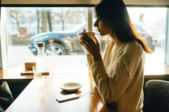 Café de consumición de la muchacha y el escuchar la música fotos de archivo