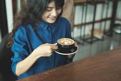 Café de consumición de la mujer asiática en tienda Fotografía de archivo