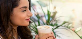 Café de consumición de la mujer en el café, disfrutando de su mañana imagenes de archivo
