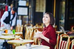 Café de consumición de la mujer francesa en café al aire libre en París, Francia imagen de archivo libre de regalías