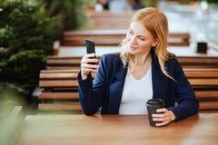 Café de consumición de la mujer hermosa en un café y un teléfono Fotografía de archivo