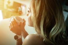 Café de consumición de la mujer hermosa por la mañana imágenes de archivo libres de regalías